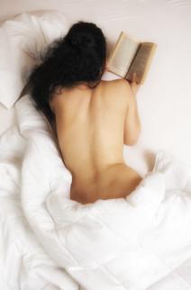 Naakte vrouw leest sexverhaal in bed